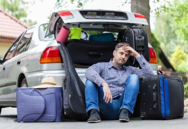 Homme assis devant sa voiture en réfléchissant comment ranger ses valises dedans