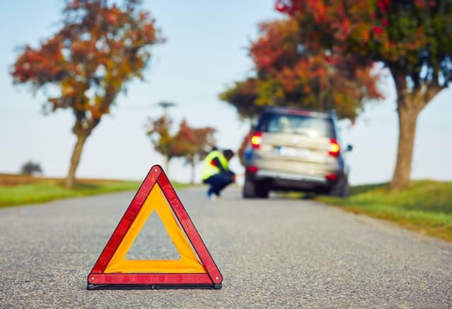Triangle de signalisation et voiture en panne